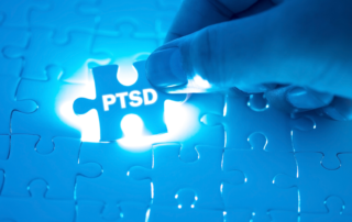 """""""PTSD"""" written on spotlighted puzzle piece being placed into a puzzle to complete it"""